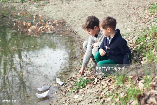 Glückliche Jungen spielen im Fluss.