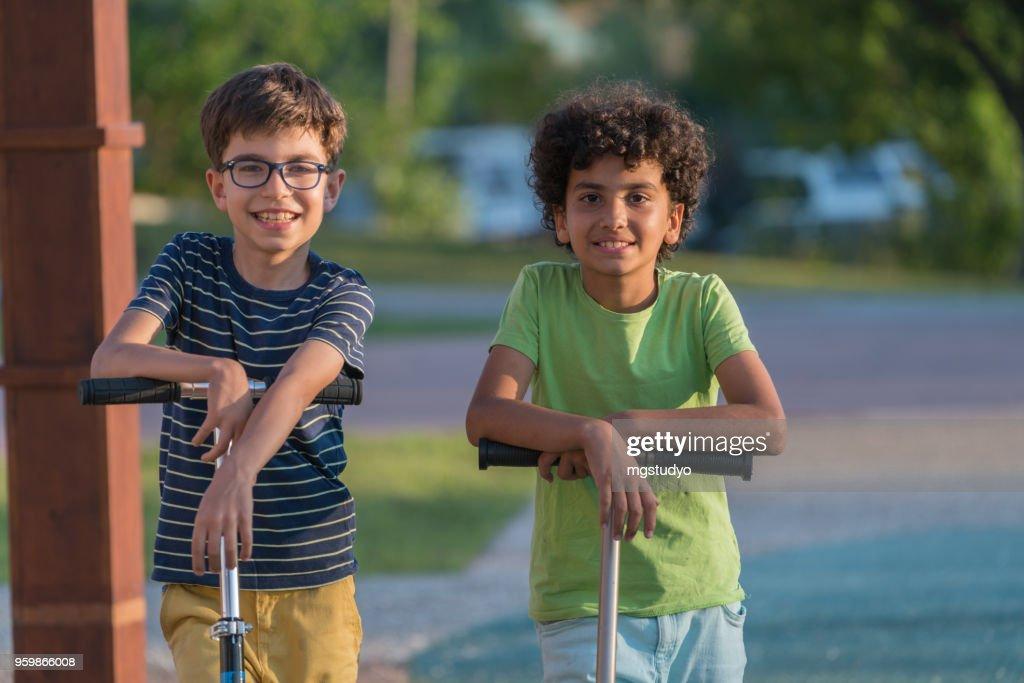 Happy Boys mit Roller in einem park : Stock-Foto