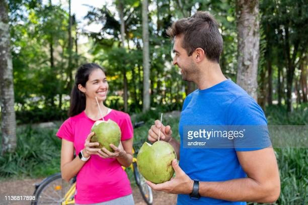 happy brazilian couple drinking coconut water after training - coconut water stock pictures, royalty-free photos & images