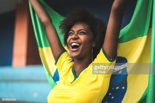 Fã brasileiro feliz comemorando em um jogo de futebol