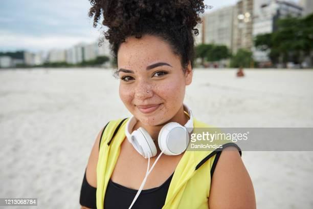 glückliche brasilianische sportlerin - dicke frauen am strand stock-fotos und bilder