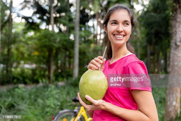 happy brazilian woman drinking coconut water after training - coconut water stock pictures, royalty-free photos & images