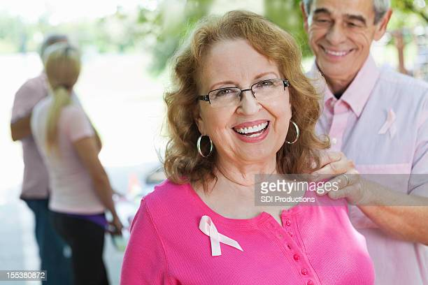 Happy breast cancer survivor with supportive spouse at charity race