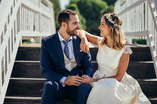 Happy bridal couple sitting on stairs holding hands - gettyimageskorea