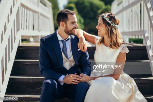 happy bridal couple sitting on stairs holding hands - wedding stock pictures, royalty-free photos & images