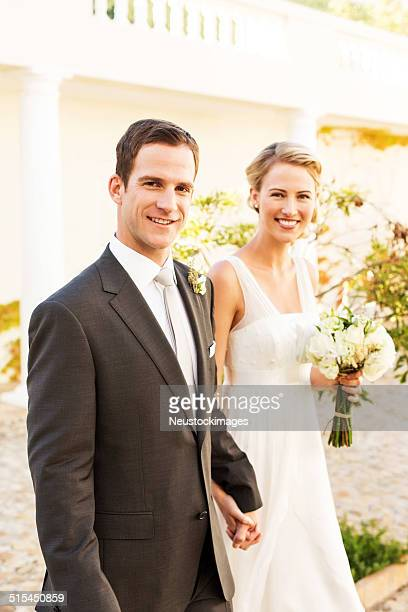 Happy Bride And Groom Holding Hands