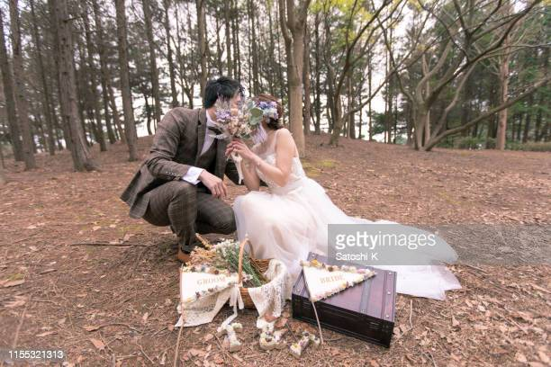 happy bride and groom kissing behind bouquet - blindfolded bride stock pictures, royalty-free photos & images