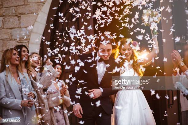 happy bride and groom leaving church and celebrating - matrimonio foto e immagini stock