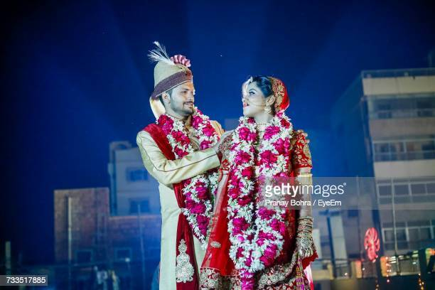 happy bride and groom looking at each other during wedding ceremony at night - indian bohra stock pictures, royalty-free photos & images