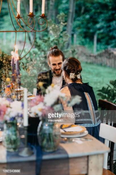 happy bride and groom sitting at festive laid table outdoors - vestimenta de negocios fotografías e imágenes de stock
