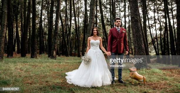 happy bride and groom standing in forest with funny dog-shaped balloon - freaky couples stock photos and pictures