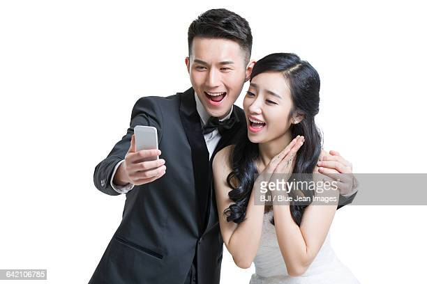 Happy bride and groom taking self portrait with smart phone