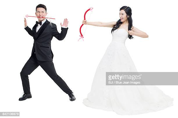 happy bride and groom with bow and arrow - funny cupid stock pictures, royalty-free photos & images
