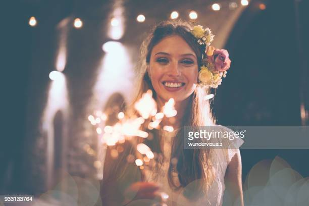 Happy bride in white wedding dress holding sparklers and celebrating