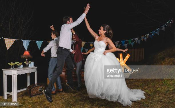 Happy bride jumping and giving high five with young man on a night field party with friends
