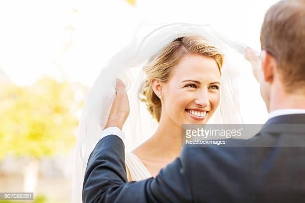 Heureuse Mariée regardant loin tout en soulevant son voile marié