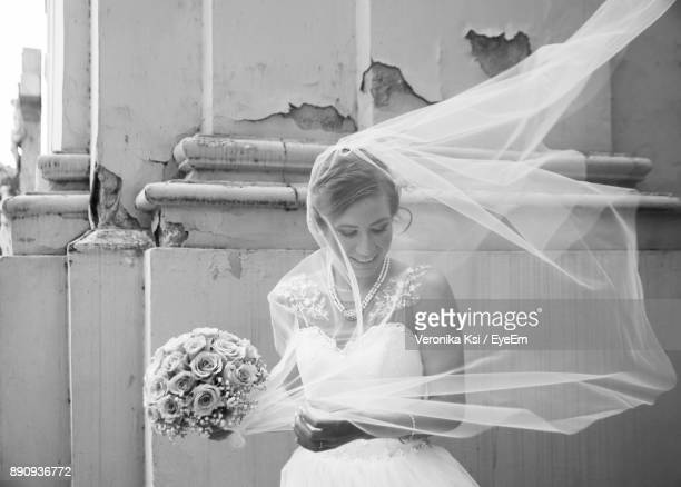 happy bride with bouquet standing outdoors - ksi stock photos and pictures