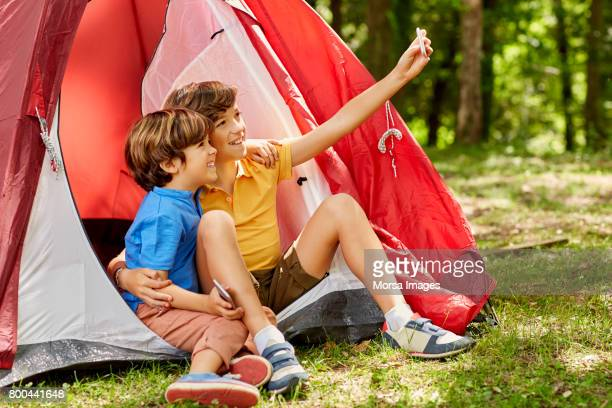 Happy brothers are taking selfie by tent in forest