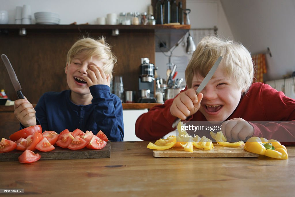 Happy brothers holding knives at table with vegetables in kitchen : Stock Photo