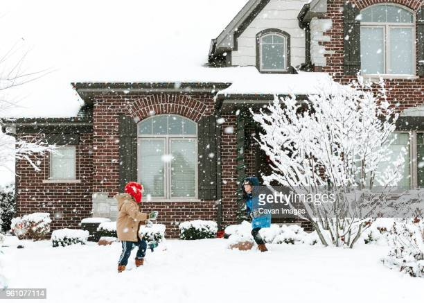 happy brothers playing with snow in yard - winter house stock pictures, royalty-free photos & images