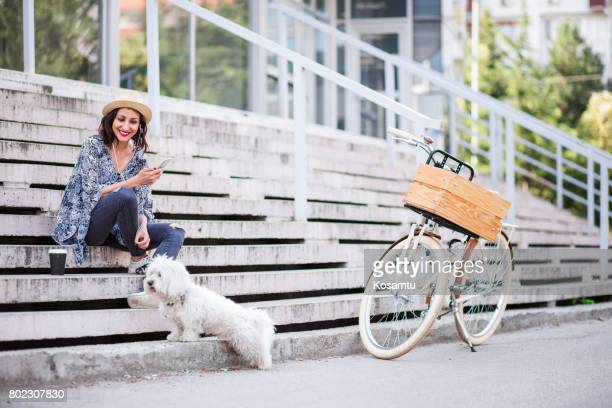 Happy Brunette Girl In Cute Hat Taking Cute Maltese Canine Out For a Walk