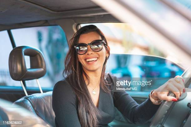 happy brunette woman driving a car - driver stock pictures, royalty-free photos & images