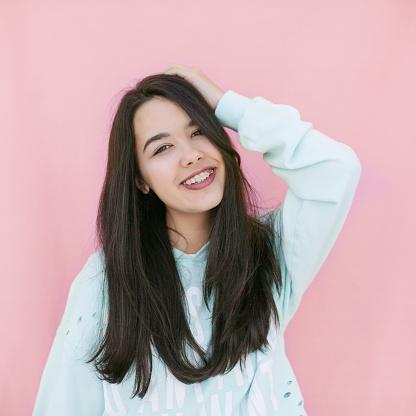 happy brunette young girl teenager in pink background - gettyimageskorea