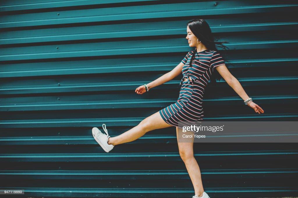 happy brunette young woman walking on street against blue wall : Stock-Foto