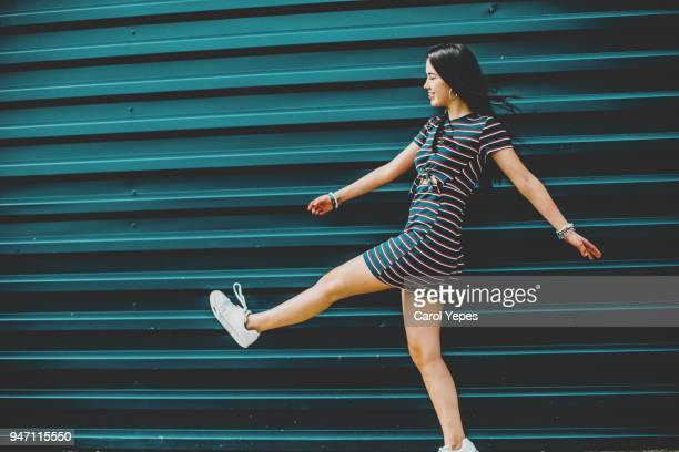 happy brunette young woman walking on street against blue wall - kleid stock-fotos und bilder