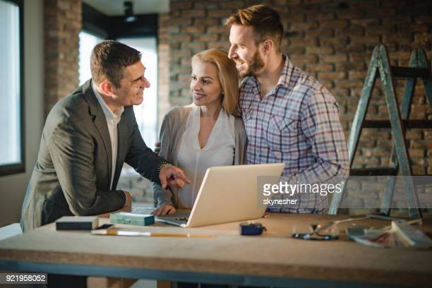 happy building contractor and young couple communicating while using computer at construction site. - building contractor stock pictures, royalty-free photos & images