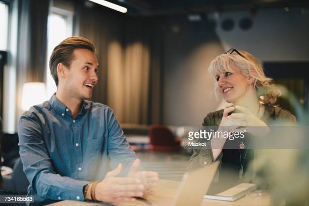 happy business colleagues discussing at conference table in board room - older woman younger man stock photos and pictures