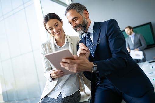 Happy business colleagues in modern office using tablet 1133767597