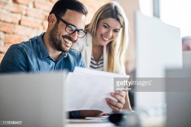 gelukkige zaken collega's die documenten op kantoor lezen. - netjes informeel stockfoto's en -beelden