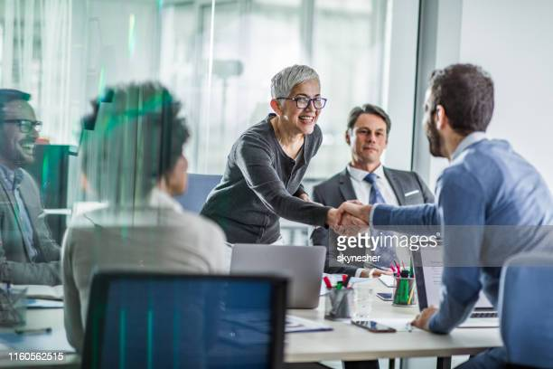 happy business colleagues shaking hands on a meeting in the office. - business meeting stock pictures, royalty-free photos & images
