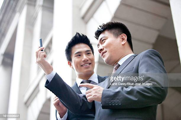 Happy business colleagues taking a good look at smart phone outdoors, Hong Kong