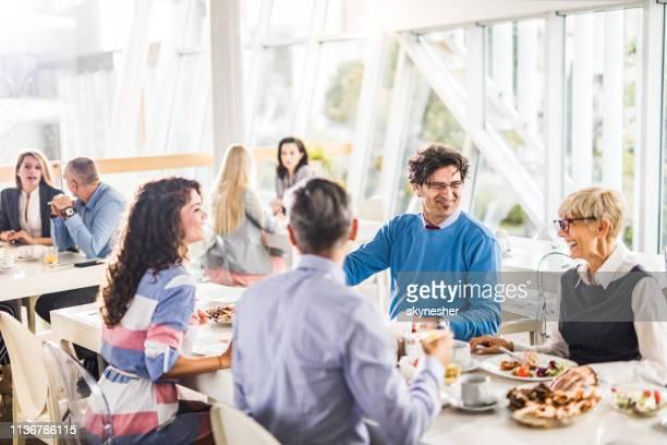 felici colleghi di lavoro che parlano durante una pausa pranzo in mensa. - lunch foto e immagini stock