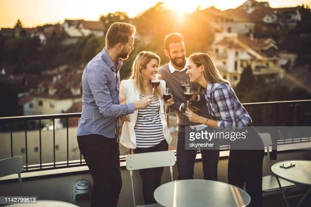 felices colegas de negocios hablando en una fiesta en la terraza al atardecer. - casual chic fotografías e imágenes de stock