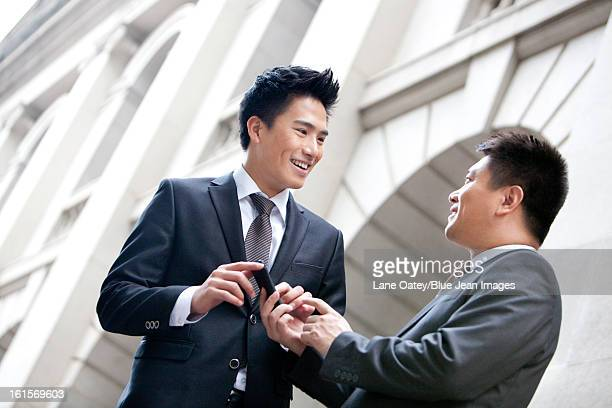 Happy business colleagues with a smart phone in front of a building, Hong Kong