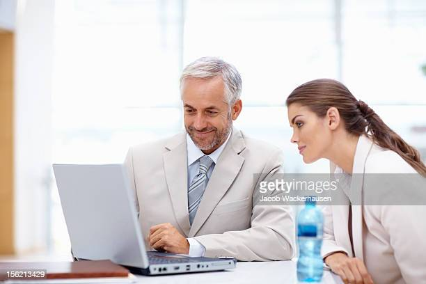 Happy business colleagues working on a laptop