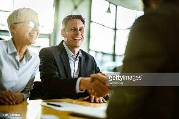 happy business couple came to an agreement with their agent in the office. - customer stock pictures, royalty-free photos & images