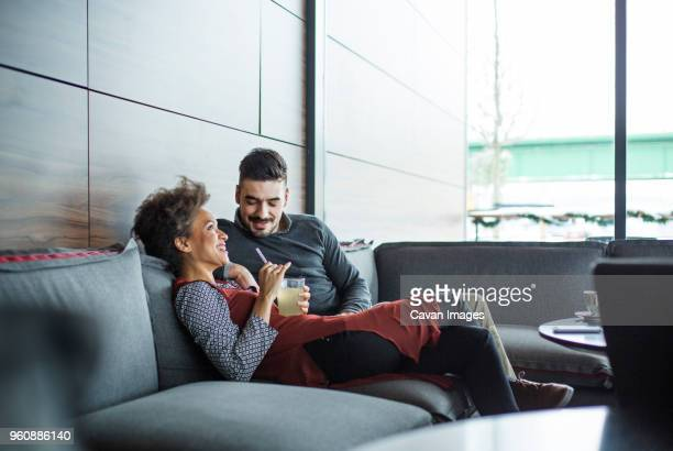 Happy business couple relaxing on sofa in restaurant