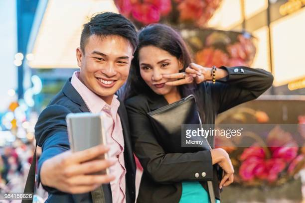 happy business couple shooting selfies kuala lumpur - downtown comedy duo stock pictures, royalty-free photos & images