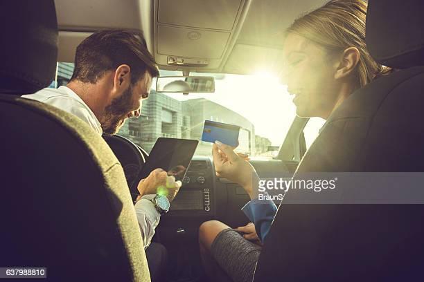 Heureux couple de professionnels achats en ligne dans la voiture.