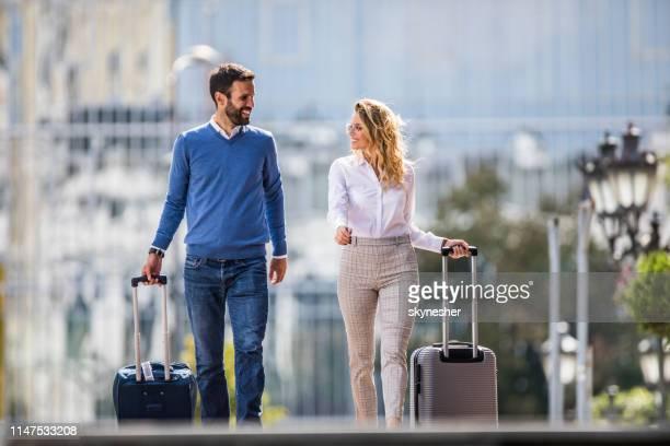 路上で彼らのスーツケースを引っ張っている間、幸せなビジネスカップルが話しています。 - 引く ストックフォトと画像