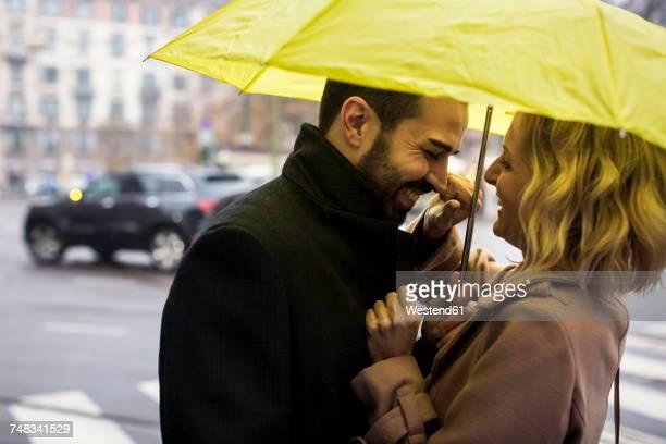 Happy business couple under umbrella in the city