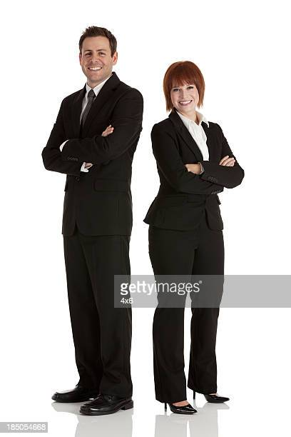 Happy business executives standing with arms crossed