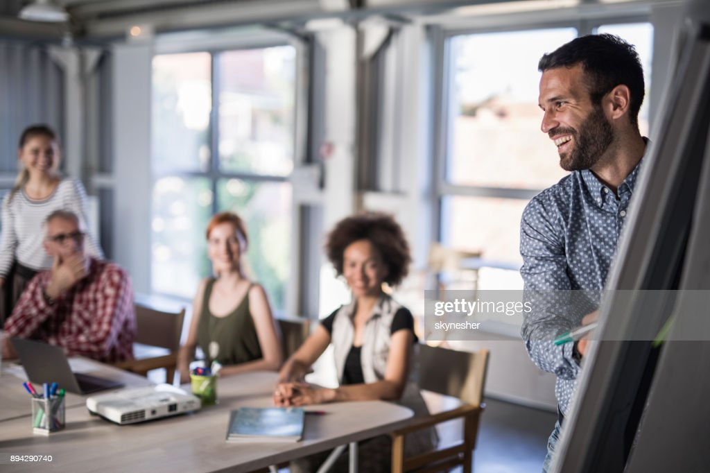 happy business leader presenting his team a new business plan on whiteboard stock photo