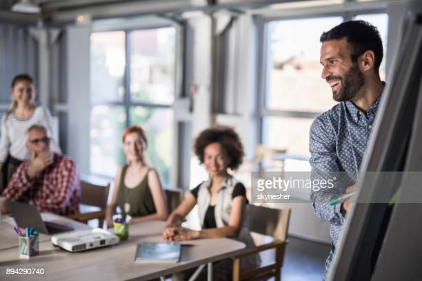happy business leader presenting his team a new business plan on whiteboard. - small group of people stock pictures, royalty-free photos & images