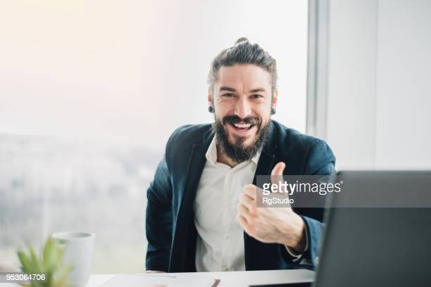 happy business man showing thumb up while sitting at office - like button stock photos and pictures