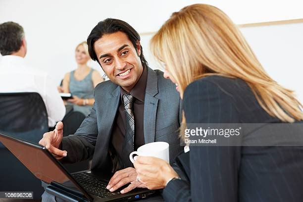 Happy Business mentor looking at laptop with client
